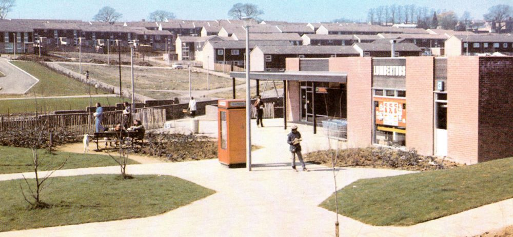 This image shows the Lumbertubs Estate when it was newly built. In the foreground is a shop with an orage telephone box and well kept grass between paths. To the rear of the image are rows of houses.