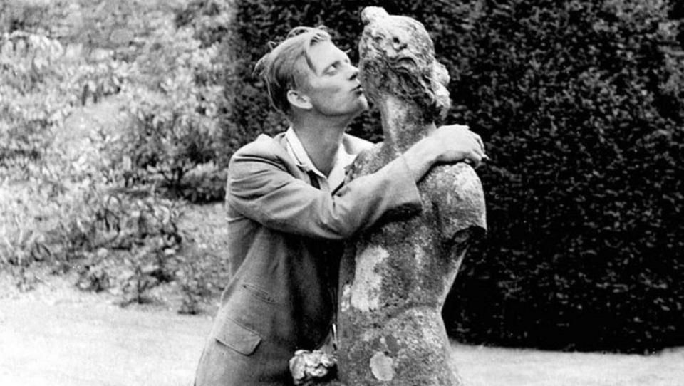 Derek Tompkins is a tall white man standing next to a stone statue of a woman with a dog next to her. He is hugging the statue and kissing its lips. He is wearing a suit and the statue is quite old with one arm missing.