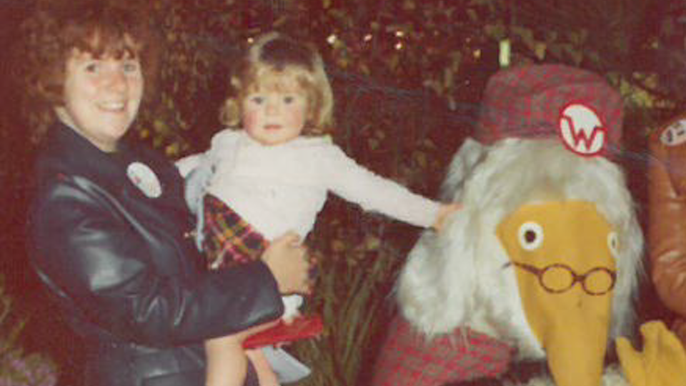 This is a picture of Jeanette Muddiman being held as a child by her Mother as she meets the Wombles mascot. They are at Weston Favell Shopping Centre. She is wearing a white top and has red shoes. Her Mum is wearing a navy blue leather mac. They are standing next to the Womble and Jeanette is touching its head with her left hand.