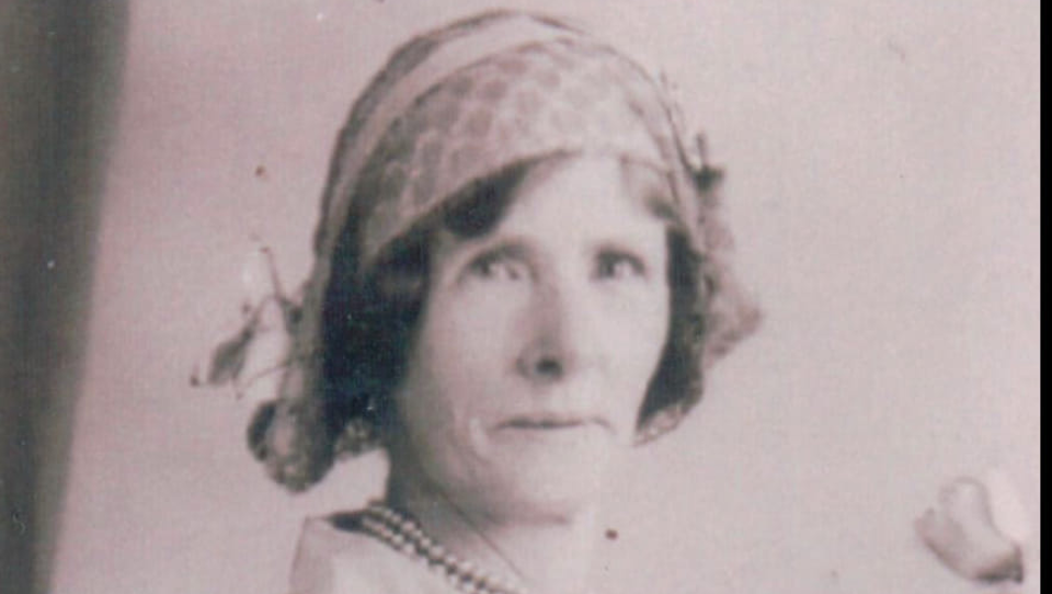 A black and white photo of Auntie Em. She is a white woman wearing a bonnet style hat. Her dark hair curls out from underneath and she is wearing a shirt and a pearl necklace.