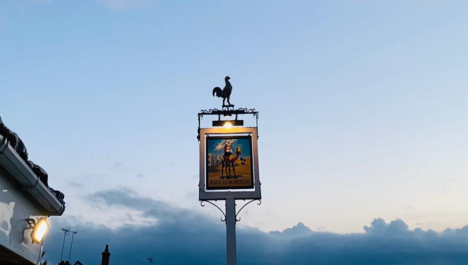 A sign for the Road to Morocco pub, which has a cockerel on the top, set against a sky with the sun setting.