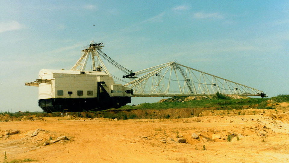 Image of a large walking dragline. The sky is blue and the ground is sand coloured. The dragline has a large body with a white top half and to the right is a large boon arm. The structure is huge.
