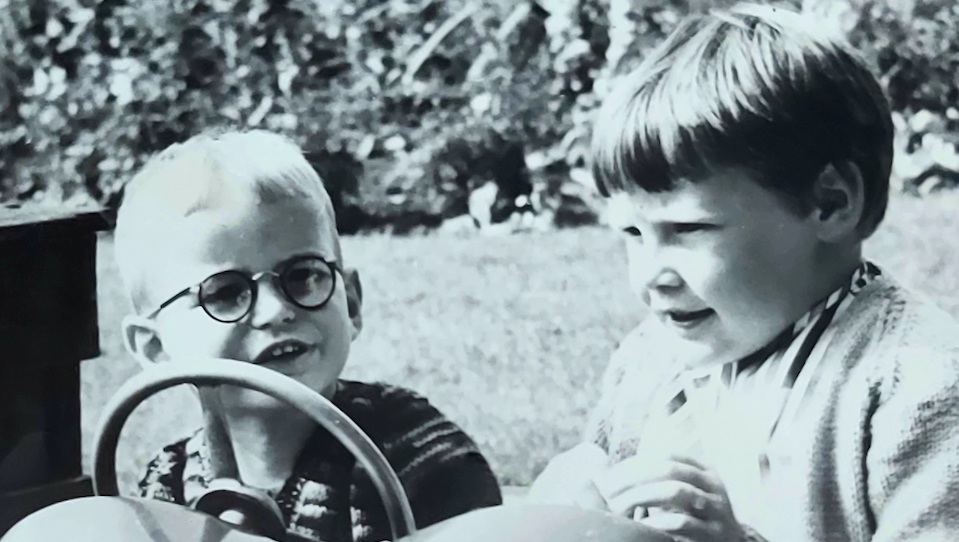 This image shows the story author as a child with his sister, they are sitting ona. tractor at Wicksteed Park in the 9160s. The image is black and white . The child to the left has short blonde hair and glasses, the older child to the right has short darker hair.